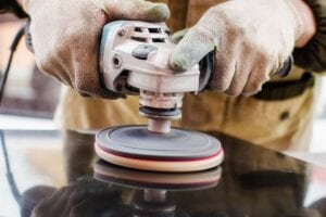Worker Polishes A Stone With A Grinder